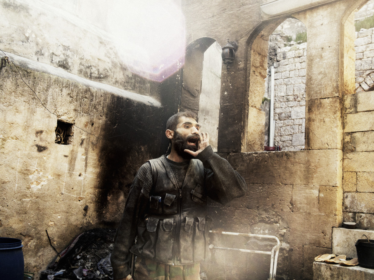 """Aleppo, Syria. March, 2013. A rebel yells """"Allahu Akbar"""" (God is Great) during close-quarters fighting in Aleppo's Old City."""