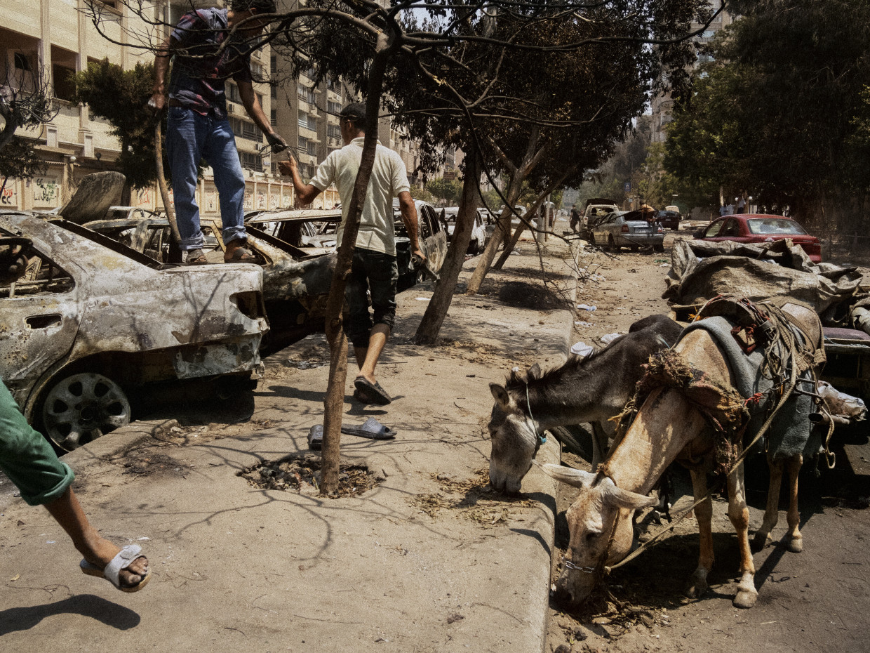 Cairo, Egypt. December, 2013. Men collect scrap metal from burned vehicles damaged during the Rabaa massacre of supporters of the Muslim Brotherhood.