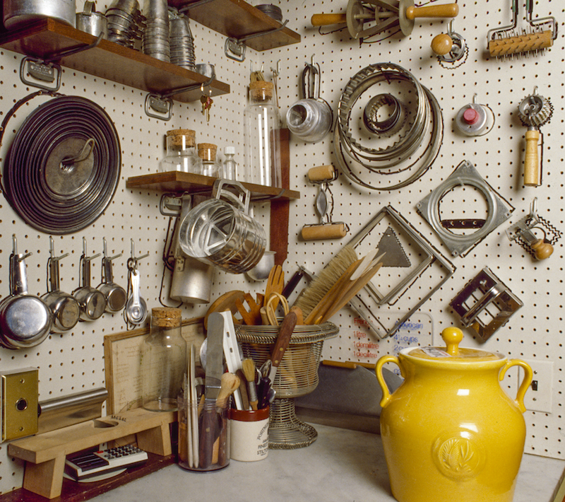 Pastry tools stored on wall in pantry.