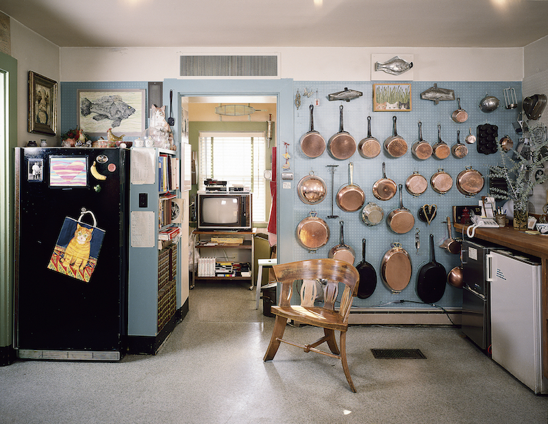 Kitchen view, west, showing copper pans and black refrigerator.